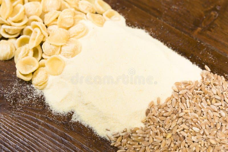 Grains de pâtes, de farine et de blé sur une table en bois image libre de droits