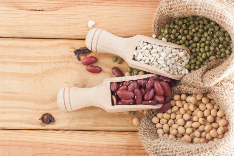 Grains entiers dans le scoop en bois sur le Tableau en bois photos stock