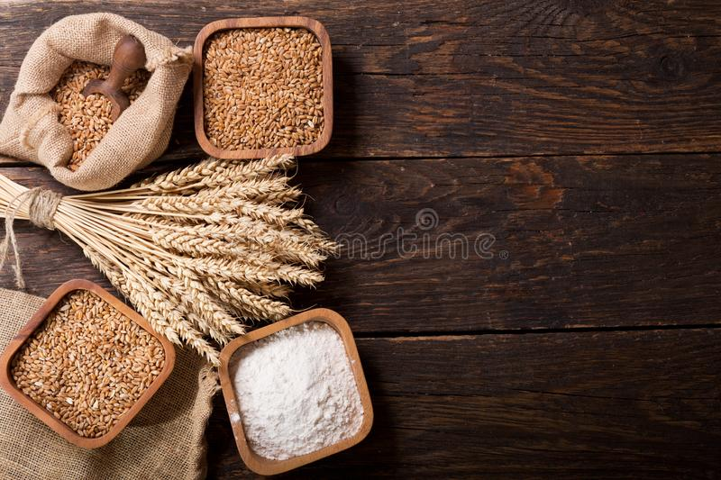 Grains, flour and wheat ears on a wooden table stock photo