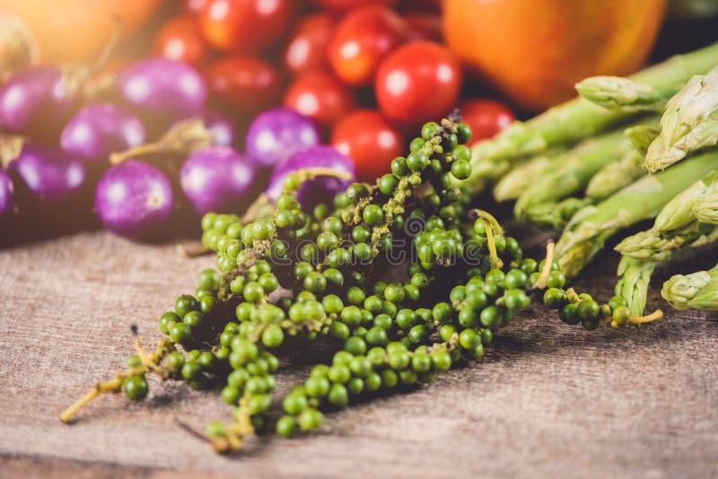Grains frais de poivron vert dans la vigne sur la table en bois et les divers genres de légumes comme fond photos stock