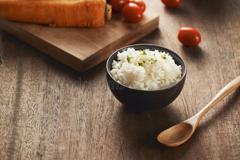 Grains of rice in a wooden bowl and ingredients for a vegetarian recipe - healthy eating concept stock photo