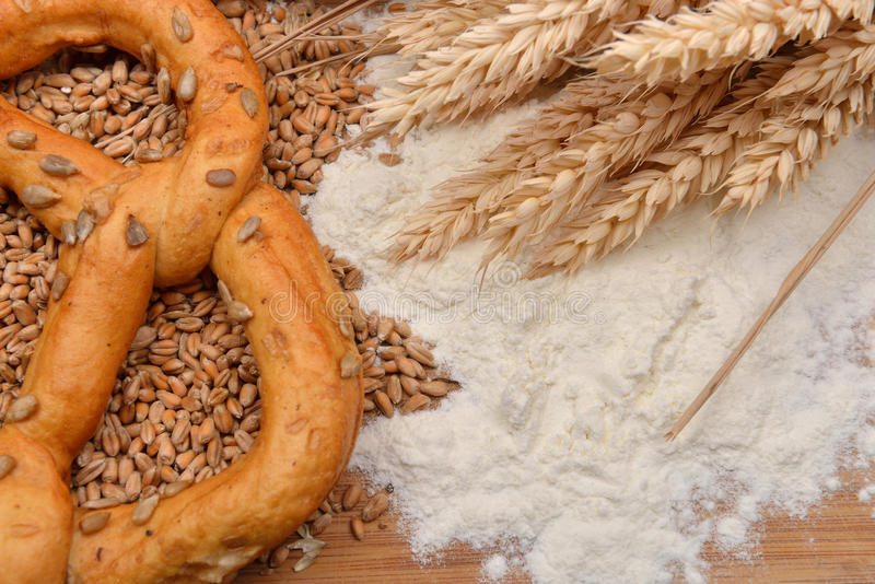 Grains, wheat ears, flour and pretzel on a wooden table. Concept stock photos