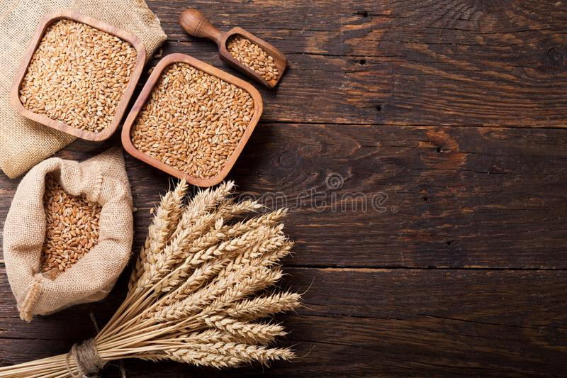 Grains and wheat ears on a wooden table royalty free stock images