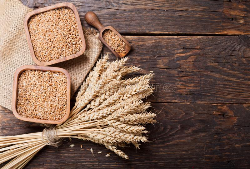 Grains and wheat ears on a wooden table royalty free stock photography
