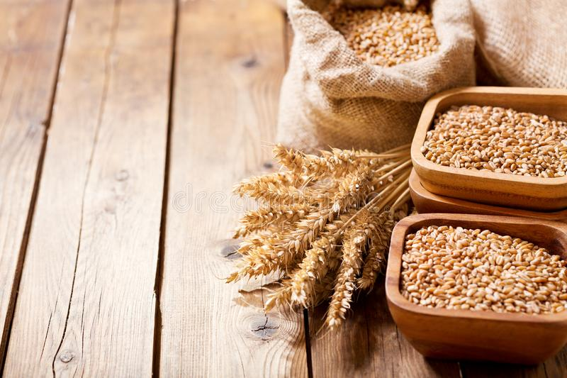 Grains and wheat ears on a wooden table stock image