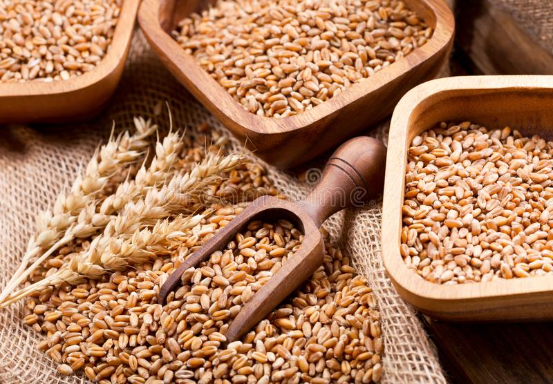 Grains and wheat ears on a wooden table stock images