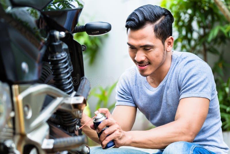 Graisse de pulvérisation d'homme dans la motocyclette images libres de droits