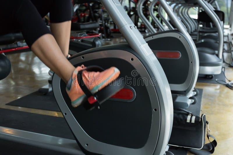 Graisse de recyclage de brûlure de femme sur la cardio- machine de bicyclette dans le gymnase de forme physique photos stock