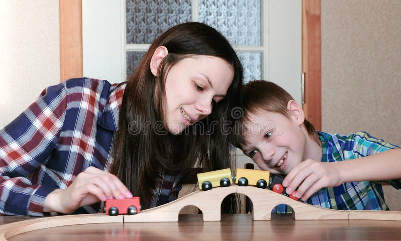 graliśmy razem Szczęśliwa mama i syn bawić się drewnianą kolej z pociągiem, furgonami i tunelowym obsiadaniem, przy stołem zdjęcie stock