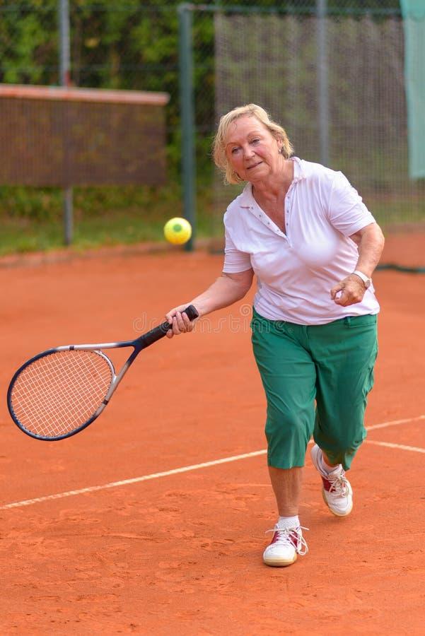 gram starszej kobiety tenisa obrazy royalty free