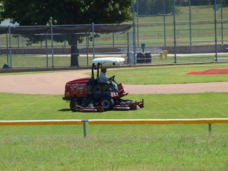 A grama que está sendo cortada em um campo de bola fotos de stock