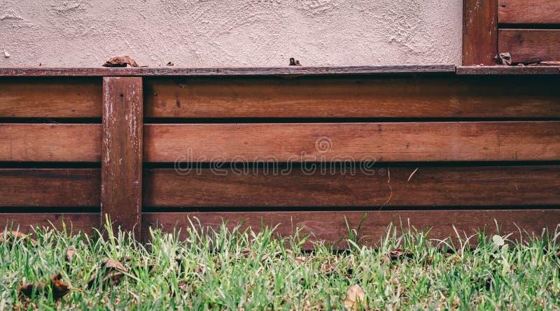 Grama verde com paneling e o muro de cimento de madeira imagens de stock