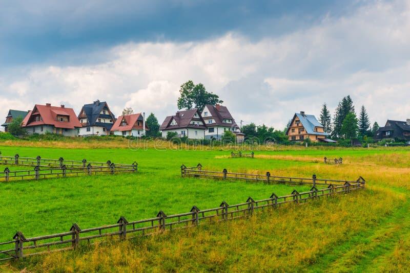 Gramado com cerca e as casas de campo de madeira fotografia de stock royalty free