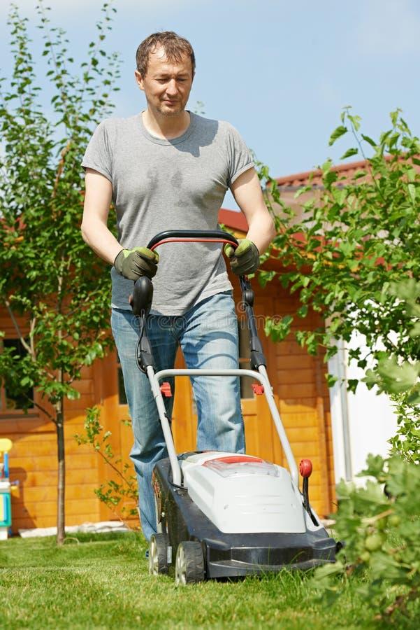 Gramado de sega do homem no quintal fotografia de stock royalty free