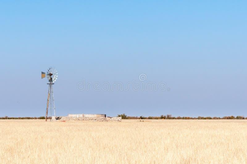 Grame a paisagem com moinho de vento e represa em Namíbia do norte fotos de stock royalty free