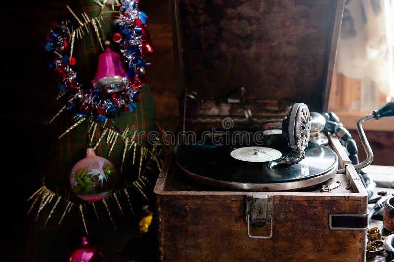 Grammofon som spelar ett rekord med vinyl på bakgrundsgarneringar, locket, träd och ljusa ljus fotografering för bildbyråer