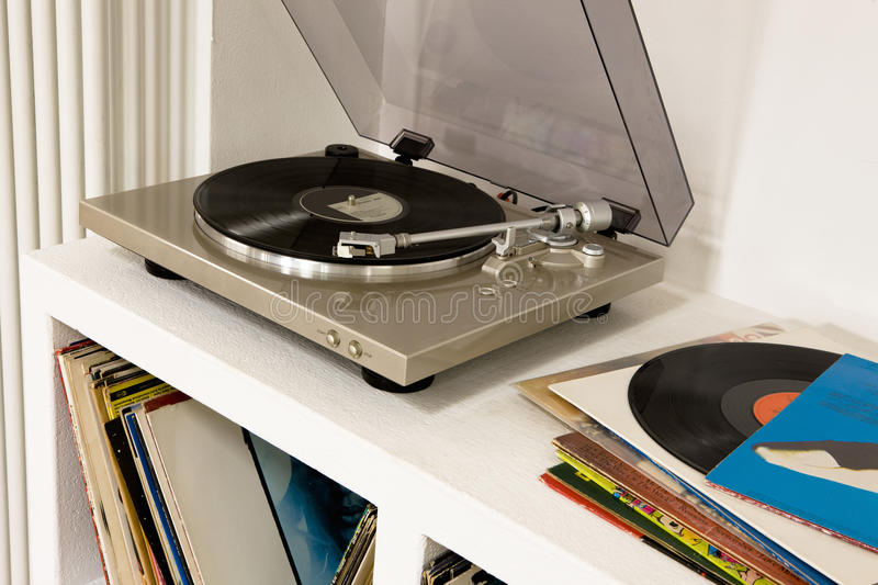 Gramophone With Vinyl Records. Closeup of a gramophone over shelf with vinyl records stock photos