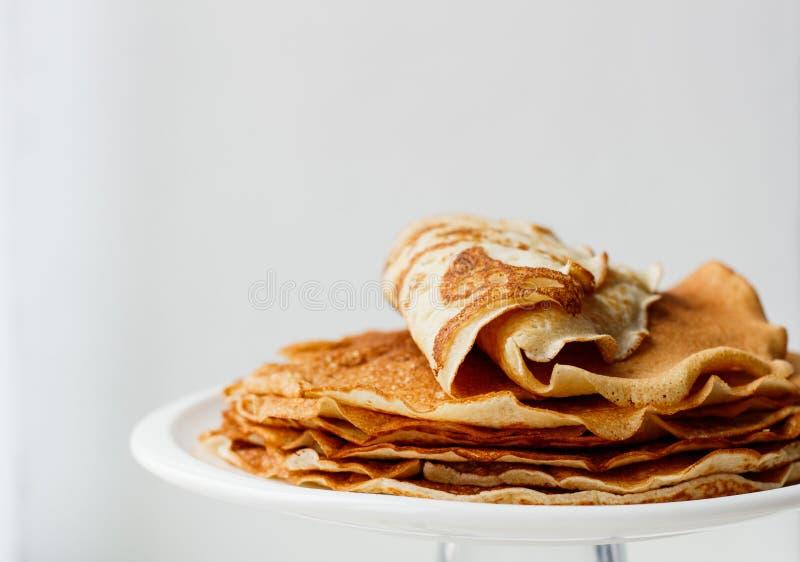 Grampo de panquecas ou de crepes dourados do fermento do trigo em um close up branco da placa em um fundo branco imagens de stock royalty free