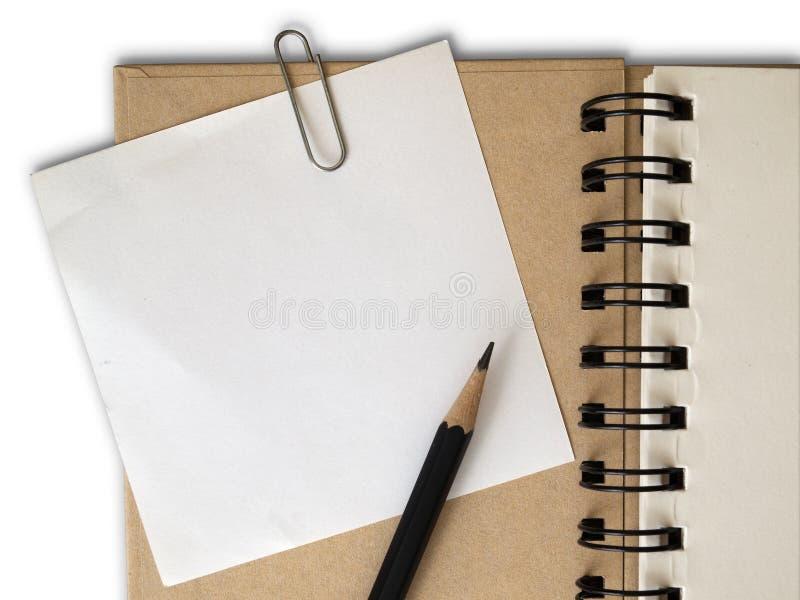Grampo de papel branco de nota no livro de nota marrom da tampa fotos de stock royalty free