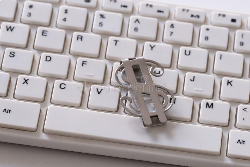 Grampo do dinheiro de metal sob a forma de um símbolo do dólar americano Peça de um teclado de computador branco O conceito do ne fotos de stock royalty free