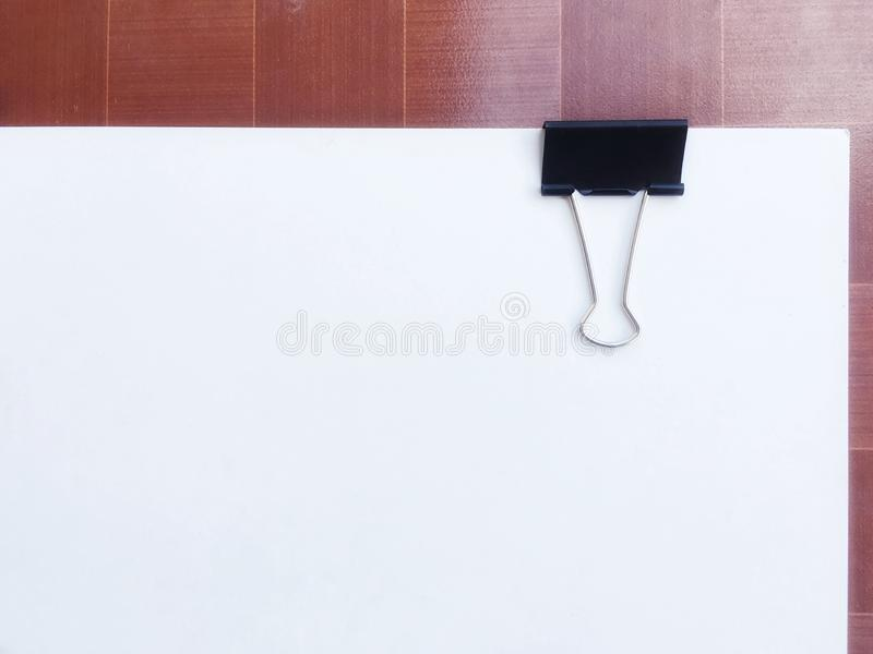 Grampo preto da pasta no Livro Branco posto sobre o fundo marrom fotos de stock