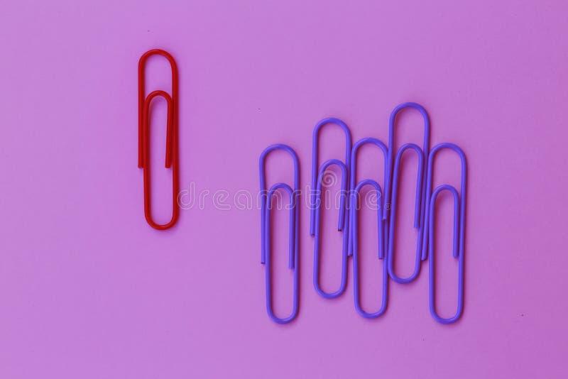 Grampo vermelho do papel colorido proeminente no fundo roxo mínimo imagens de stock