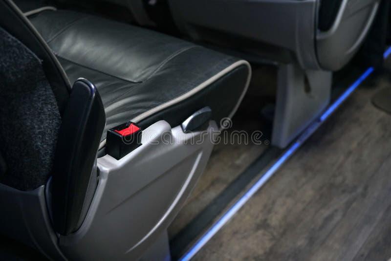 Grampo vermelho do seatbelt no assento do ônibus Os cintos de segurança são obrigatórios em treinadores interurbanos no Reino Uni imagens de stock royalty free