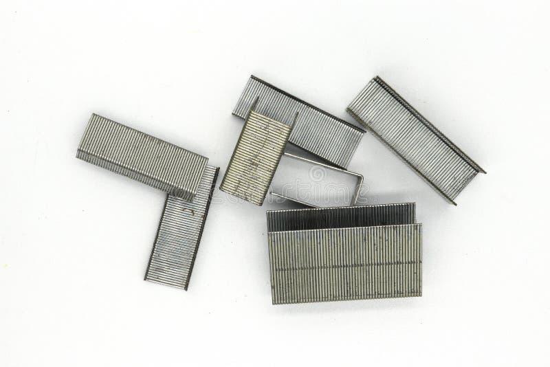 Grampos do metal para o grampeador isolado no fundo branco imagem de stock