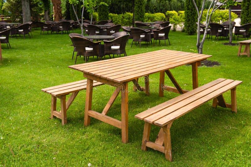 Gran banco natural de madera y mesa al aire libre foto de archivo