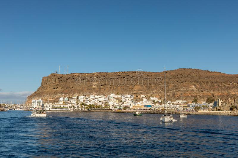 Gran Canaria, Canary Islands in Spain - December 16, 2017: Sailboats, ferry and boats in the ocean in front of the old. Gran Canaria, Canary Islands in Spain royalty free stock image