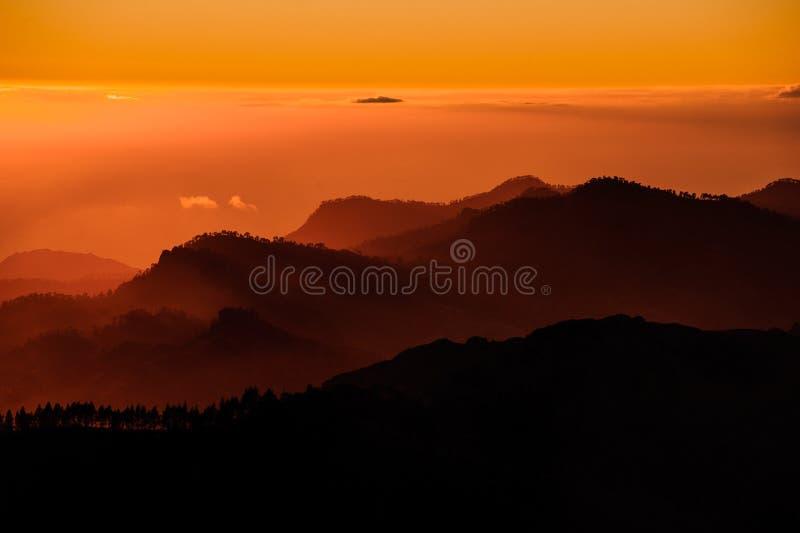 GRAN CANARIA, ESPAÑA - 6 DE NOVIEMBRE DE 2018: Paisaje magnífico de la puesta del sol en colinas hermosas anaranjadas en las mont fotos de archivo libres de regalías