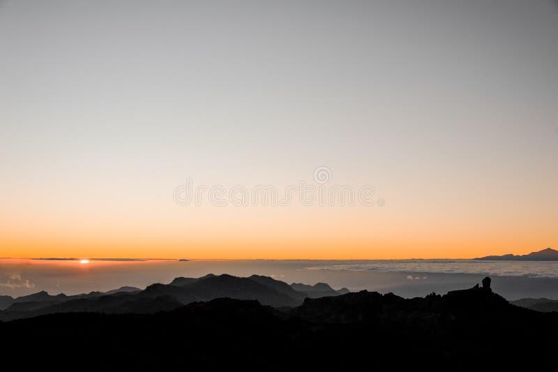 GRAN CANARIA, SPANJE - NOVEMBER 6, 2018: Mooie zonsopgangmening van Roque Nublo-berg onder dikke wolken en helder stock afbeelding