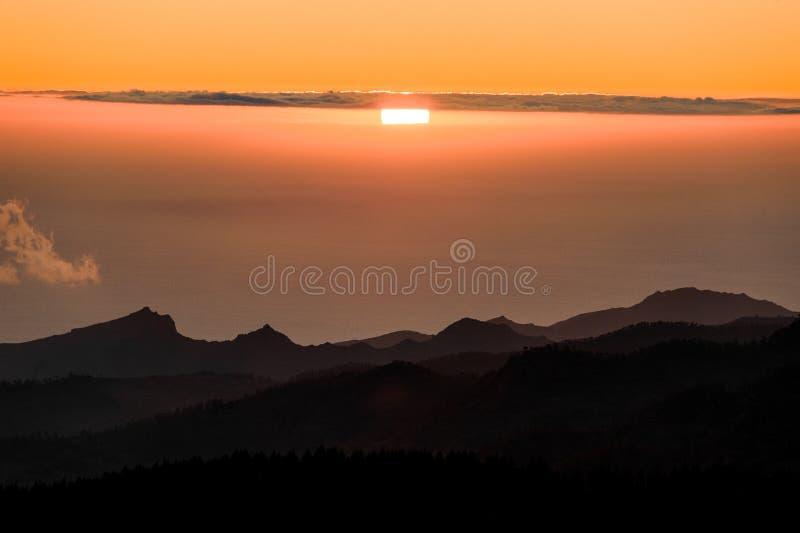 GRAN CANARIA, SPANJE - NOVEMBER 6, 2018: Ochtendmening van Roque Nublo-berg onder dikke wolken en helder zonlicht stock afbeelding