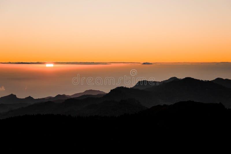 GRAN CANARIA, SPANJE - NOVEMBER 6, 2018: Zonsopgangmening van Roque Nublo-berg onder dikke wolken en helder zonlicht stock afbeeldingen