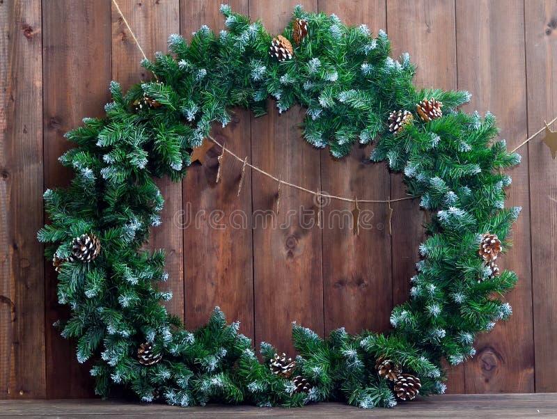 Gran guirnalda de la Navidad con los conos del pino en un fondo de madera foto de archivo