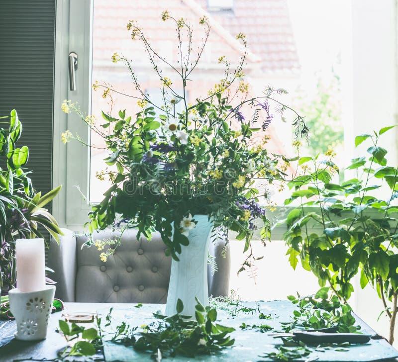 Gran manojo de las flores salvajes del verano en el florero blanco en la tabla en sala de estar en la ventana Forma de vida caser fotografía de archivo libre de regalías