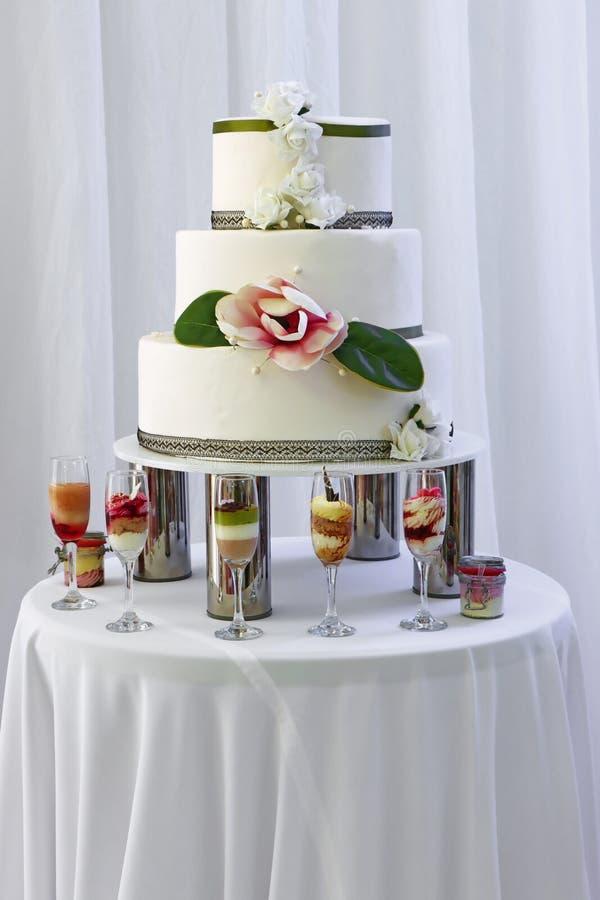 Gran pastel de boda con tres pisos decorados con rosas blancas y rosas rosas imagenes de archivo