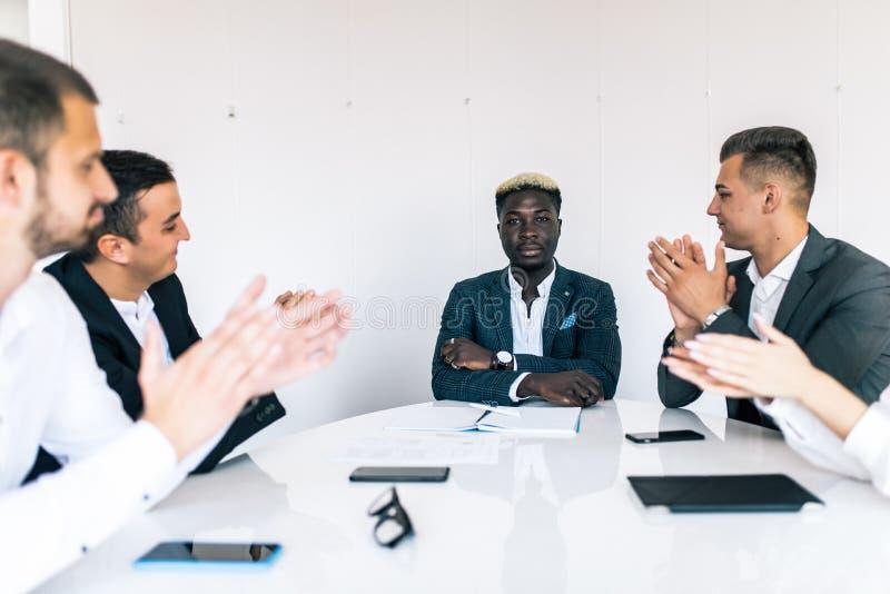 Gran presentación Grupo de hombres de negocios felices en la ropa de sport elegante que se sienta junto en la tabla y que aplaude imagen de archivo