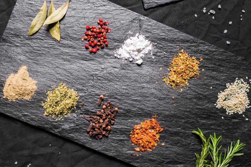 Gran selección de diversas especias y semillas coloridas del contraste en pizarra imagen de archivo