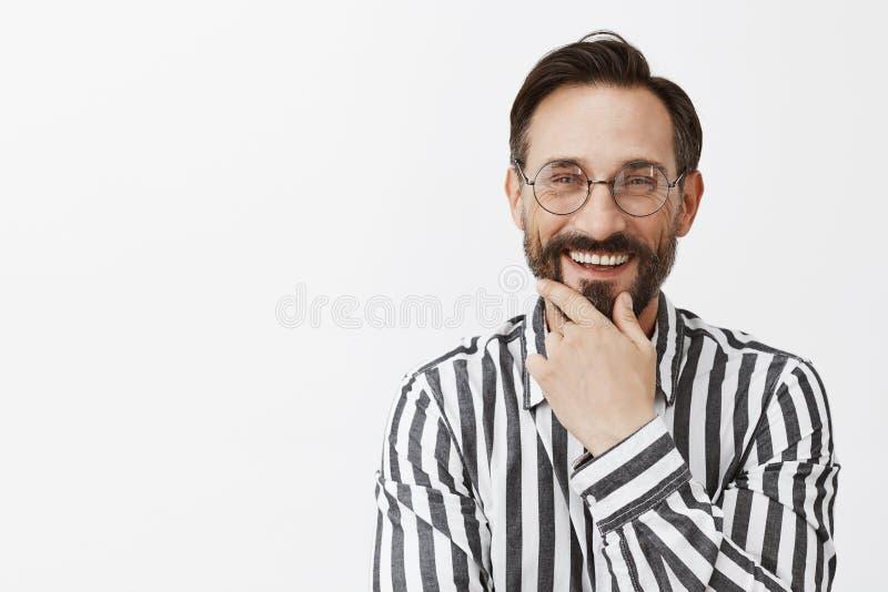 Gran sugerencia, trabajo agradable Satisfecho y satisfecho amistoso-mirando al hombre de negocios en vidrios, barba de frotamient fotografía de archivo libre de regalías