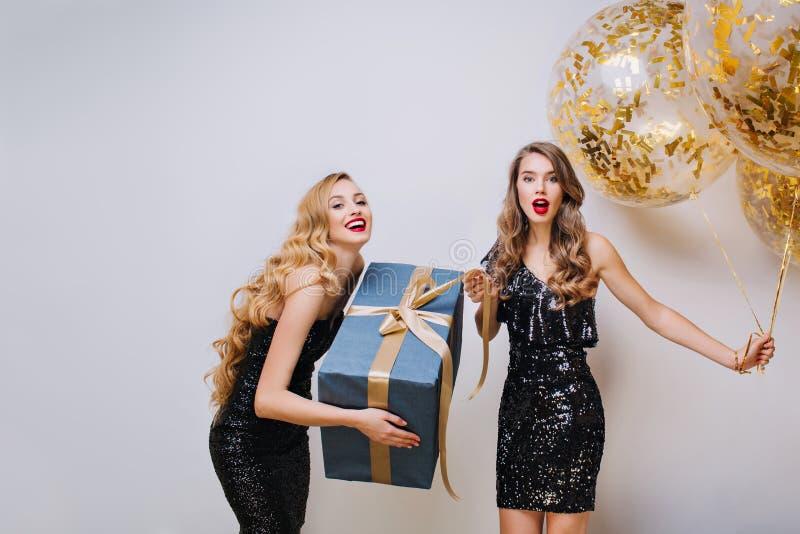 Gran tiempo del partido del feliz cumpleaños de dos mujeres jovenes divertidas encantadoras en el fondo blanco Vestidos de lujo n fotografía de archivo libre de regalías