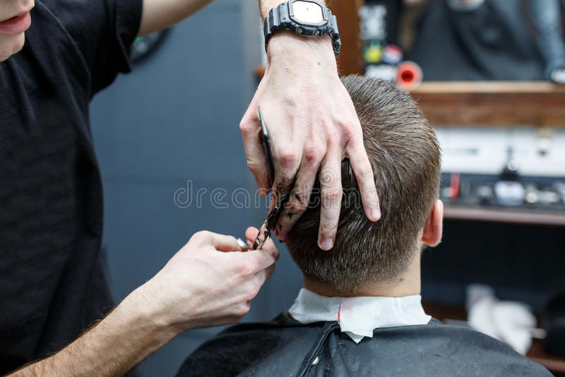 Gran tiempo en la barbería Hombre barbudo joven alegre que consigue corte de pelo del peluquero mientras que se sienta en silla e foto de archivo libre de regalías