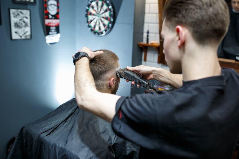 Gran tiempo en la barbería Hombre barbudo joven alegre que consigue corte de pelo del peluquero mientras que se sienta en silla e imagenes de archivo