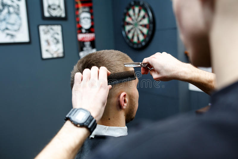 Gran tiempo en la barbería Hombre barbudo joven alegre que consigue corte de pelo del peluquero mientras que se sienta en silla e fotografía de archivo