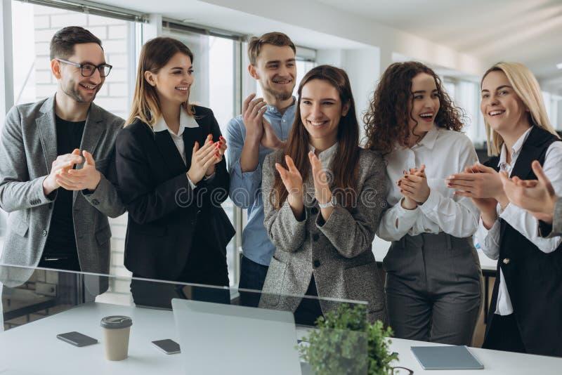 ?Gran trabajo! El equipo acertado del negocio est? aplaudiendo sus manos en el puesto de trabajo moderno, celebrando el funcionam fotos de archivo