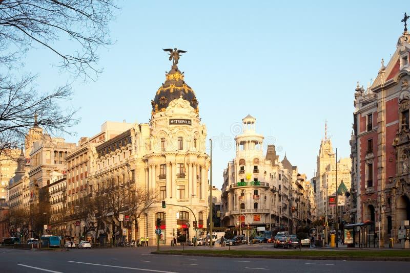 Gran via och den iconic metropolisbyggnaden sourrounded vid spansk arkitektur för trational på soluppgång royaltyfri foto