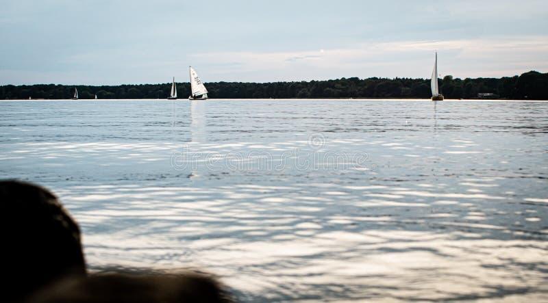 Gran visión sobre un lago tranquilo con los barcos de navegación foto de archivo