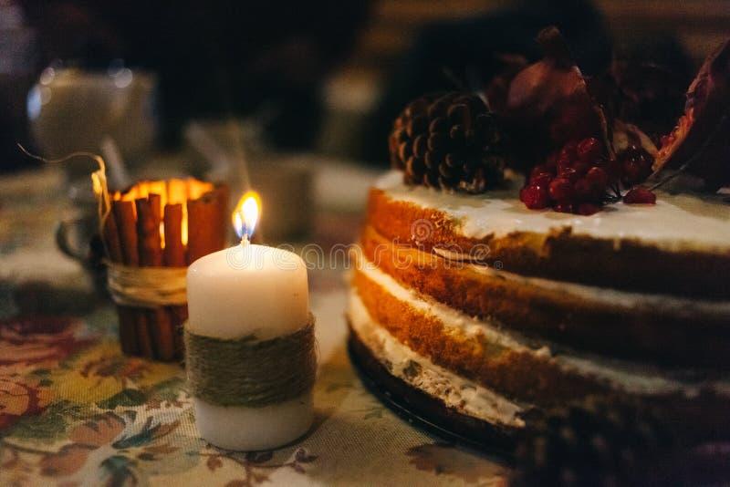 Granaatappel gelaagde cake in het licht van een dikke die kaars in een hennepkoord wordt verpakt royalty-vrije stock afbeelding