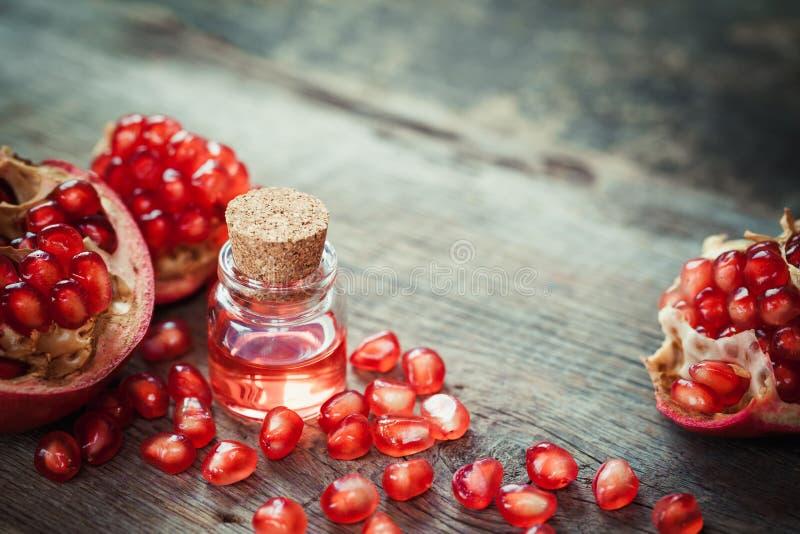 Granaatappelolie in fles en granaatfruit met zaden stock afbeelding