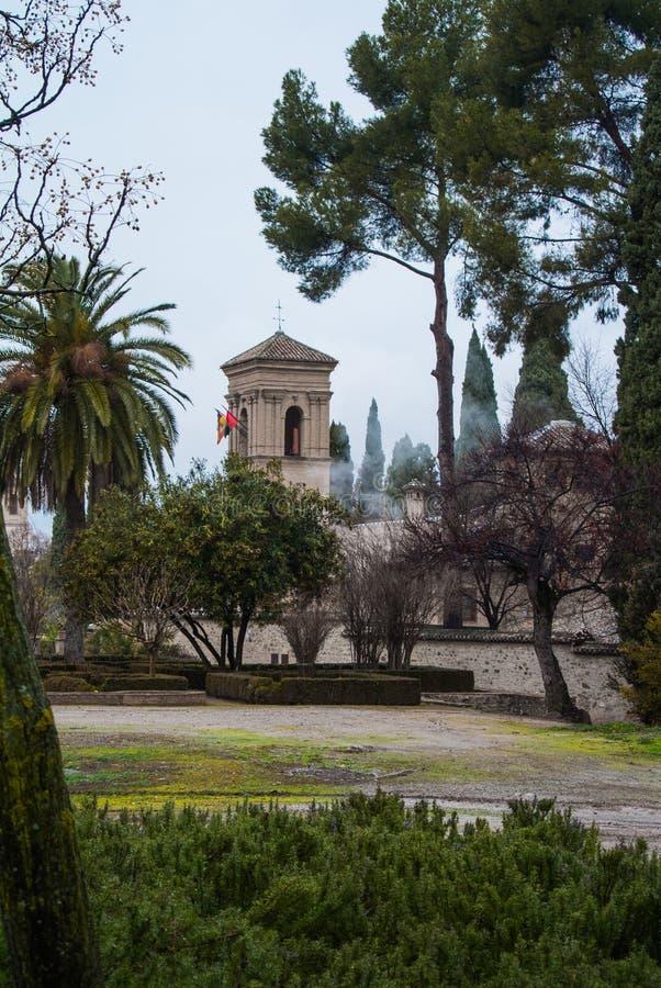 GRANADA, ESPANHA - 10 DE FEVEREIRO DE 2015: Uma vista a uma torre com as bandeiras no dia nevoento chuvoso na jarda de Alhambra foto de stock
